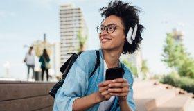 Portrait of a happy girl with headphones using her smartphone