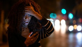Surprised woman reading bad news on her phone on street at night