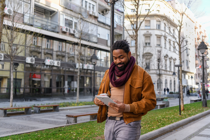Portrait of a Handsome African Man with Coffee Walking in the City Streets, Using a Digital Tablet.