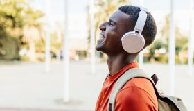 Happy man with closed eyes laughing in the street while listening to music