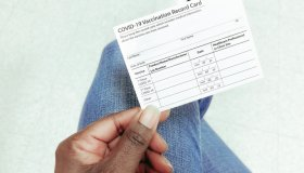 Woman Holds COVID-19 Vaccination Record Card
