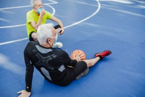 Two active senior men with face masks on basketball field taking a break from sport activity