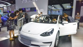 In Tesla's exhibition hall, a Tesla car surrounded by...