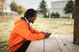 Smiling man surfing the net on smartphone in public park