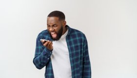 Angry Young Man Shouting On Mobile Phone While Standing Against White Background